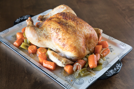 Roasted Chicken with a golden crust and vegetables on a wooden table background Imagens