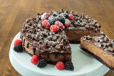 A decadent Chocolate Mousse Cake with chocolate ganache and topped with Raspberries, Blackberries and chocolate curls on a wood table Stock Photo