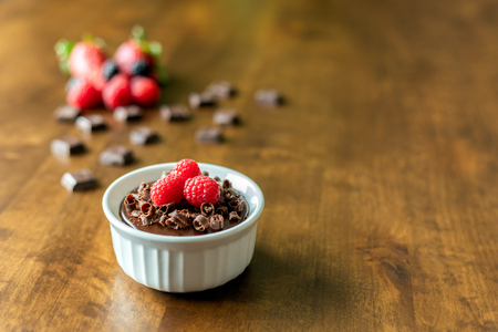 A decadent Chocolate Mousse Cake with chocolate ganache and topped with Raspberries, Blackberries and chocolate curls on a wood table in a ramekin dish
