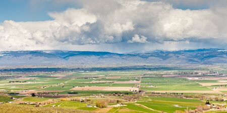 A panoramic view of Ellensburg, WA with a thunderstorm in the distance on a sunny day