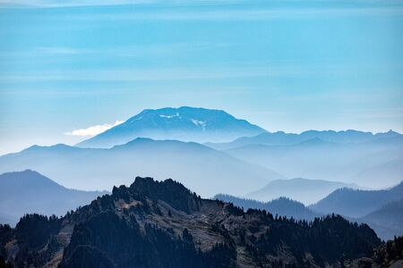 Beautiful layers of misty mountains with Mt. St. Helens in the distance and Eagle Peak in the foreground as seen from Paradise in Mt. Rainier National Park in Washington state