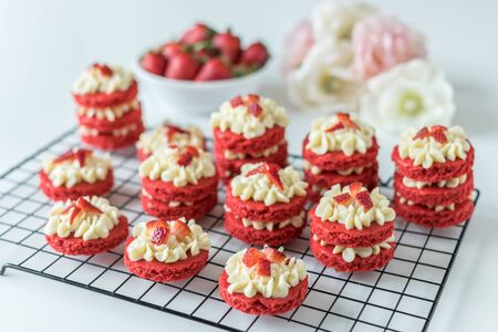 Miniature Red Velvet Cakes with cream cheese frosting and fresh strawberry topping on a cooling rack