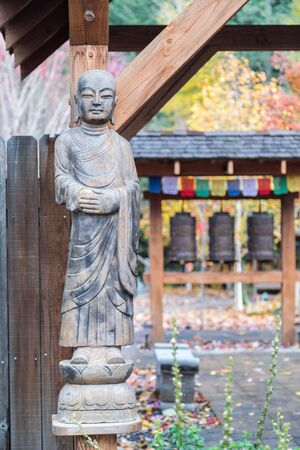 Statue of Buddha with bells and autumn colors in the background