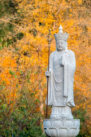 Ksitigarbha Buddha, a Bodhisattva, stone statue with yellow fall colors in the background
