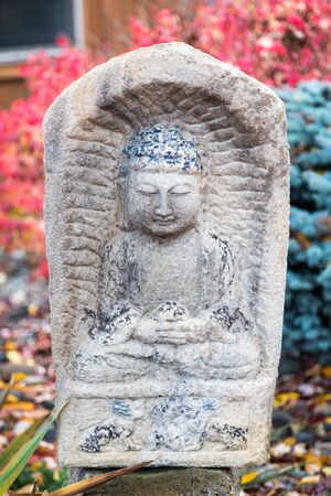 Stone carved Buddha statue in the Lotus Pose with fall colors in the background