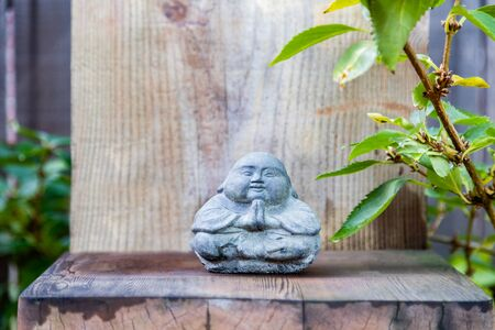 Thai style stone Buddha with praying hands in a zen setting Reklamní fotografie