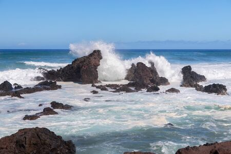 Waves crashing into lava rocks on Mauis North Shore at Hookipa Lookout on the Hawaiian Island Reklamní fotografie
