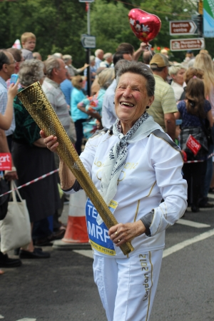 senior olympics: Bedford, England - July 21 - Woman dressed as an Olympic athlete, carrying an Olympic torch happy to be in the carnival at the bi-annual Bedford River Festival, England on 21 July 2012