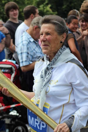 Bedford, England - July 21 - Woman dressed as an Olympic athlete, carrying an Olympic torch expresses relief at the end of the parade at the bi-annual Bedford River Festival, England on 21 July 2012