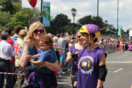 Bedford, England - July 21 - Girl on rollerblades skates alongside mother and child at the bi-annual Bedford River Festival in England on 21 July 2012 Editorial