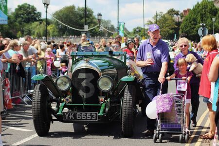 Bedford, England - July 21 - An old car accompanies the Canine Partners charity in the carnival at the bi-annual Bedford River Festival in England on 21 July 2012