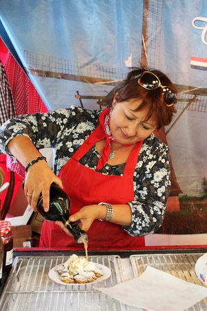 Bedford, England - July 21 - Lady prepares traditional Dutch pancakes in the European market at the bi-annual Bedford River Festival on 21 July 2012 in England Editorial