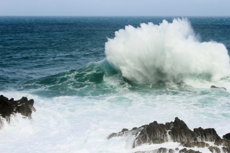 A big wave hitting a rock and crashing into the air Stock Photo