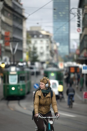 earphones: Young woman commuting in a bicycle while listening to music in Basel, Switzerland at twilight