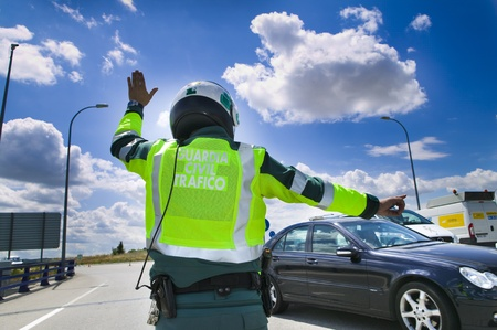 Guardia civil, spanish road traffic police, stopping a car on the roadside.