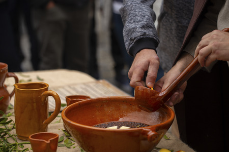 "A man is preparing burnt (traditional Galician hot drink made with flamed ""orujo"", sugar and lemon)"