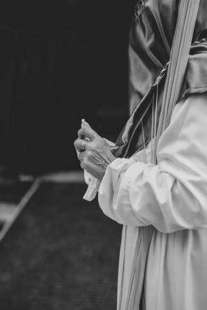 Woman putting on gloves during a procession in Holy Week Stok Fotoğraf