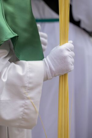Close up of a white glove in a procession, Holy Week