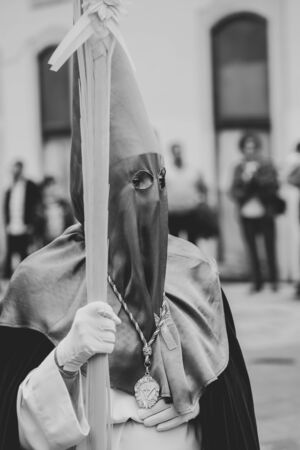 Hooded person touching belly in procession, Holy Week Banque d'images