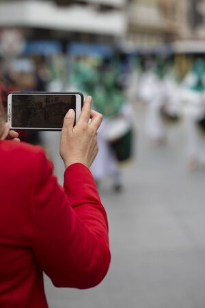 Woman taking a photo of the procession, Holy Week Stock fotó