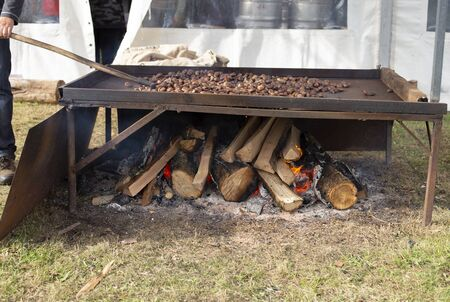 A man is roasting chestnuts Stock fotó