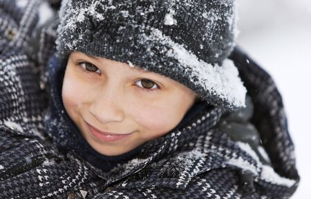 close up portrait young boy outside in the snow Banco de Imagens