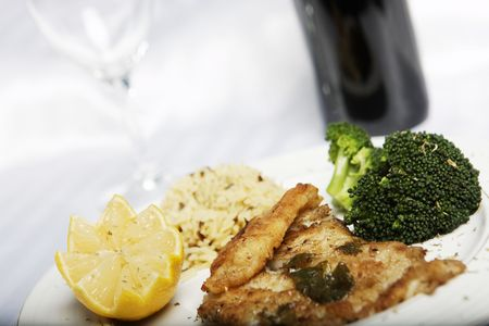 fish meal with selective focus and wine bootle and glass in the background photo