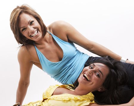 two beautiful woman looking at camera while smiling on a white background photo