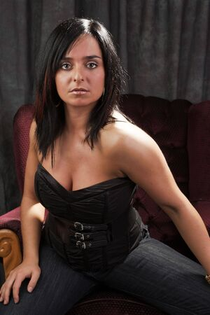 cute woman looking at the camera while sitting on a sofa photo