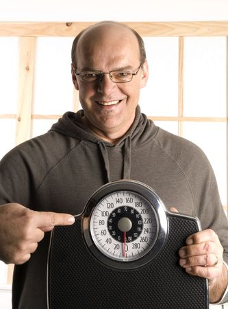 man smiling with a weight scale