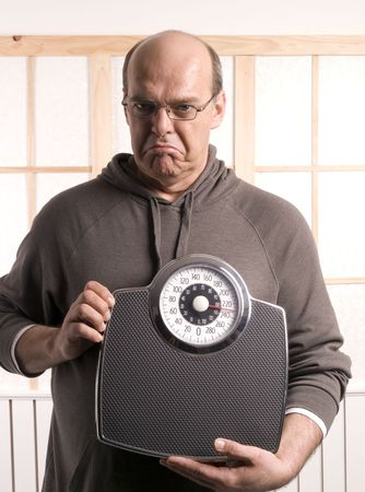 unhappy man looking at is weight Stock Photo