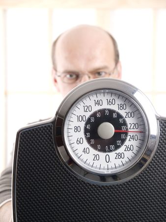 man behind a weight scale. Focus on the scale photo