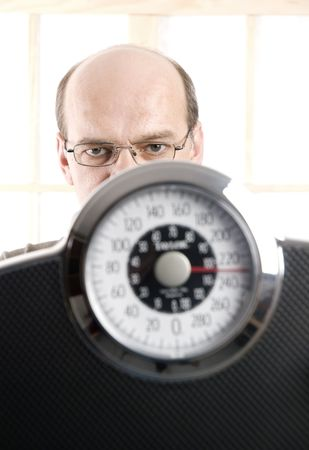 a man behind a weight scale. focus on the face photo