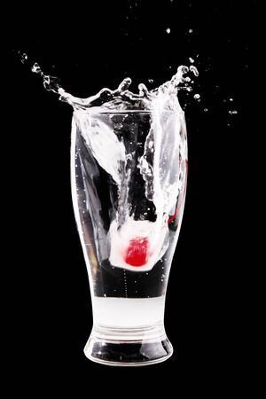 glass of water with a cherry inside the ice cube splashing photo