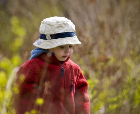 young boy in the nature with blur background around him photo