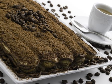 tiramisu dessert on white with coffee grain and espresso cup photo