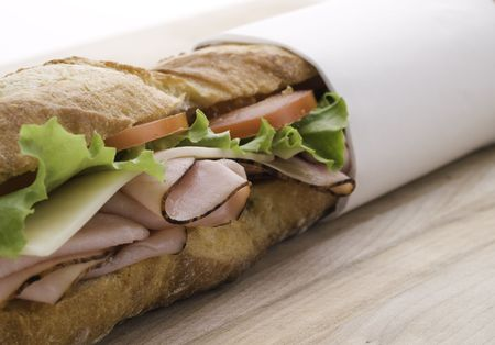 fresh submarine sandwich with ham,tomato,cheese and salad on a wooden board photo