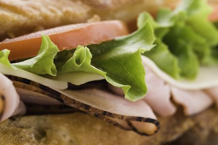 fresh macro submarine sandwich with ham,tomato,cheese and salad. Shallow depth of field Stock Photo