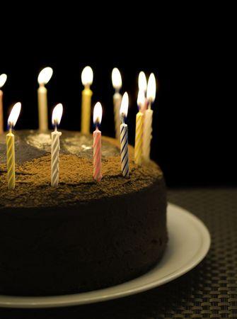 pastel de chocolate: pastel de chocolate de cumplea�os con velas encendidas en la parte superior. De fondo Negro y poca profundidad de campo. Foto de archivo