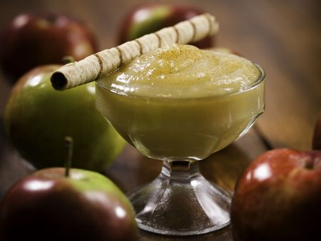 stewed: apple sauce dessert (stewed apple) on a wooden table with whole apples around. Shallow depth of field.