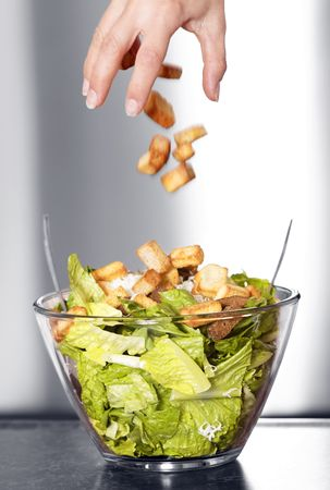Preparation of a caesar salad in a glass bowl. Movement blur of crouton falling in the salad. Selective black and white with shallow depth of field. Stockfoto