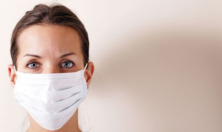 h1n1: woman with brown hair and a medical mask for protection again influenza. Shallow depth of field. Copy space for your text.