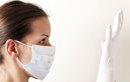 medical field: woman with brown hair and a medical mask for protection again influenza. Shallow depth of field. Copy space for your text.