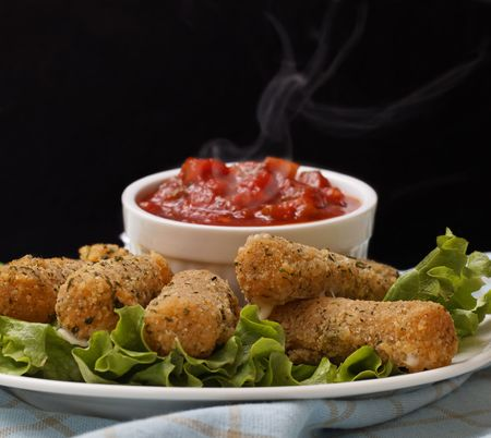 mozzarella: cheese sticks appetizer on salad with very hot salsa sauce. Smoke on the salsa with a black background.