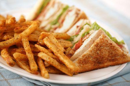 매운 감자 튀김 하얀 접시에 치킨 클럽 샌드위치. 아주 얕은 피사계 심도.