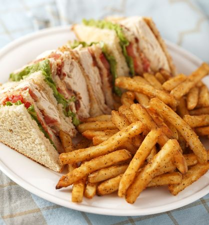 chicken club sandwich on a white plate with spicy french fries. Very Shallow depth of field.
