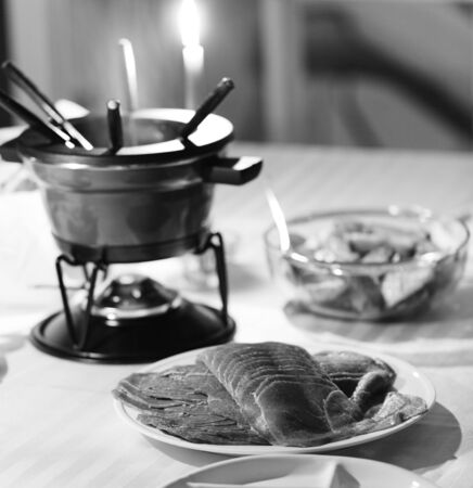 black and white photography with meat fondue dish  on a table. Very shallow depth of field. Stockfoto