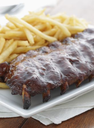 baked ribs with french fries on the side. Meat meal.  Stock Photo
