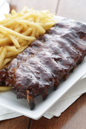 baked ribs with french fries on the side. Meat meal.  Imagens