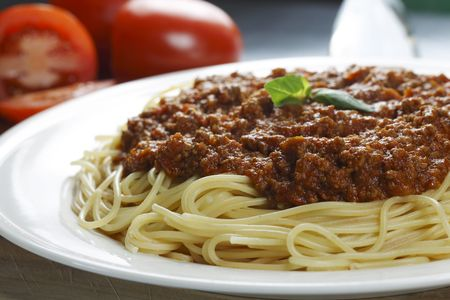 meat dish: spaghetti meal on a white plate with meat sauce. Shallow depth of field.